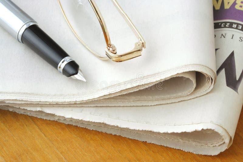 Zeitung, Gläser und Feder lizenzfreies stockbild