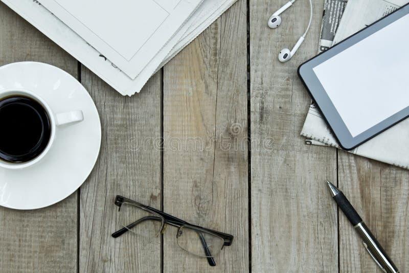 Zeitungen, digitale Tablette und Kaffeetasse auf Holztisch lizenzfreies stockbild