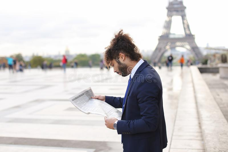 Zeitungsmannlesezeitungsartikel nahe Eiffelturm lizenzfreies stockbild