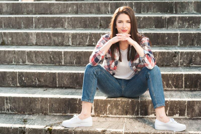 Zeker aantrekkelijk meisje die zich buiten op steentreden bevinden stock afbeelding