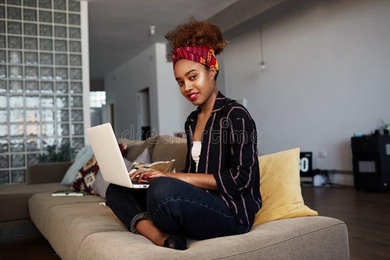 Zeker Amerikaans Afrikaans wijfje die blogger ver aan digitale netbook met Internet-tekst werken Afrikaanse vrouw royalty-vrije stock fotografie