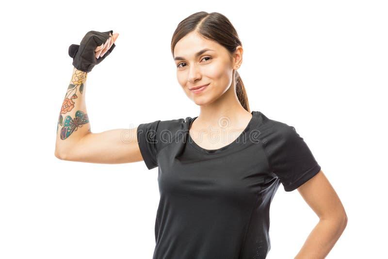 Zeker Atletisch Wijfje die Haar Bicepsen over Witte Backgrou buigen stock fotografie