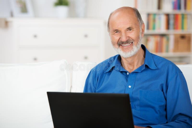 Zeker bejaarde die laptop met behulp van royalty-vrije stock afbeeldingen