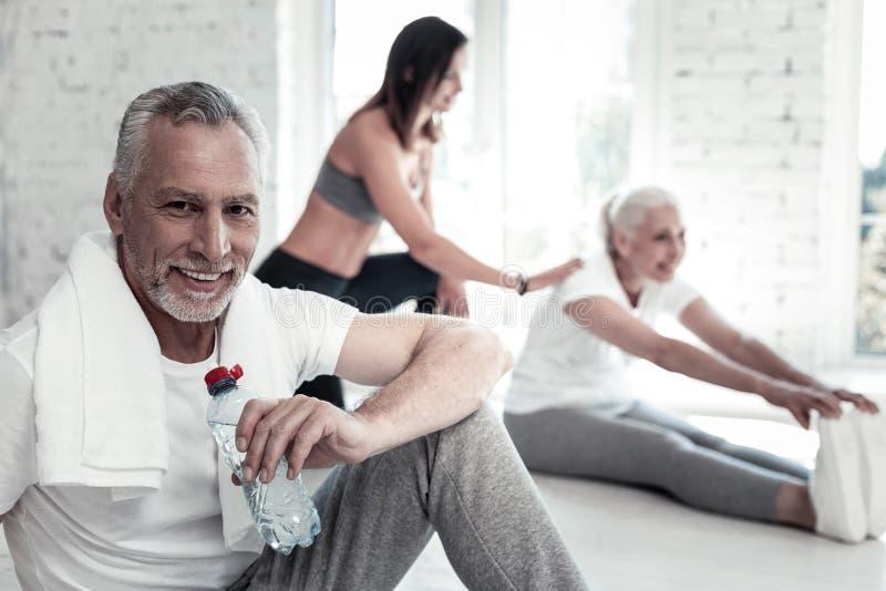 Zeker bejaarde drinkwater na gymnastiekzitting stock afbeeldingen