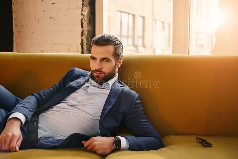 Zeker het voelen De ontspannen knappe jonge zakenman in modieus kostuum rust in bank op kantoor stock foto's
