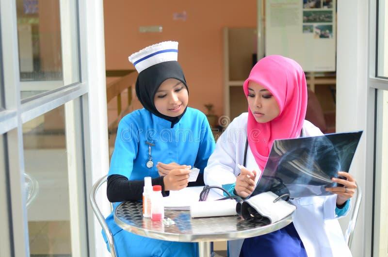 Zeker Moslimarts en verpleegster bezig gesprek bij het ziekenhuis royalty-vrije stock foto