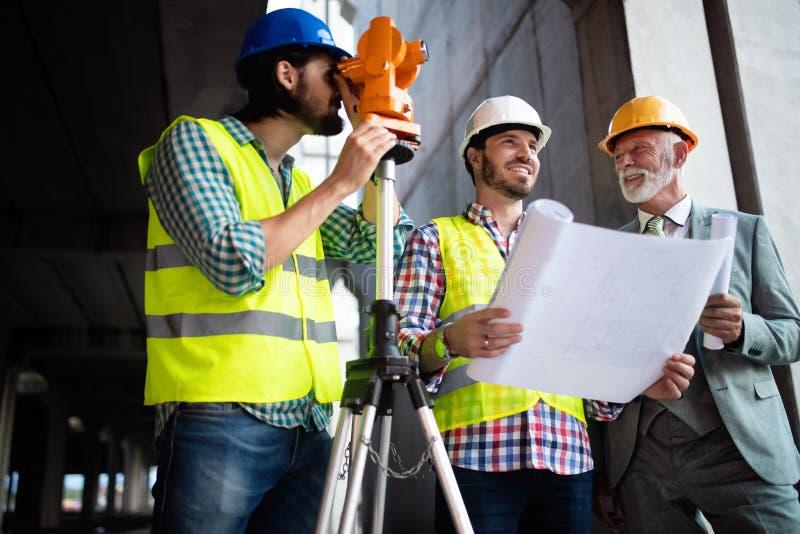 Zeker team van architecten en ingenieurs die aan bouwwerf samenwerken stock afbeelding