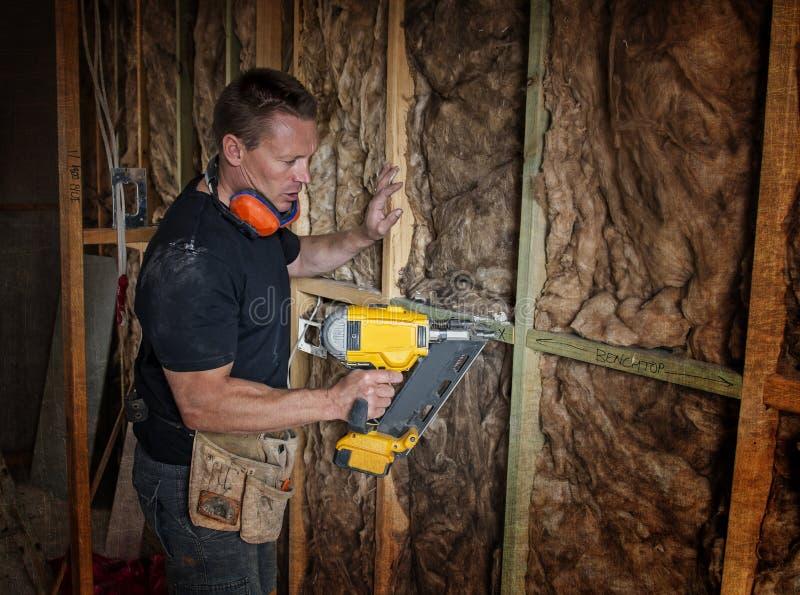 Zeker van de aannemerstimmerman of bouwer mensen werkend hout met elektrische boor bij industriële bouwwerf in installatie a royalty-vrije stock afbeeldingen