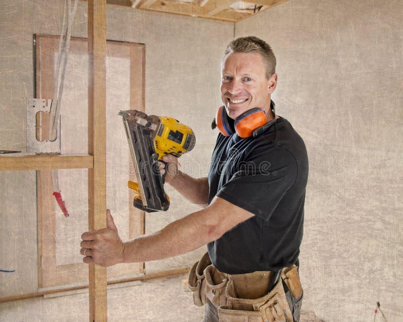 Zeker van de aannemerstimmerman of bouwer mensen werkend hout met elektrische boor bij industriële bouwwerf in installatie a stock foto