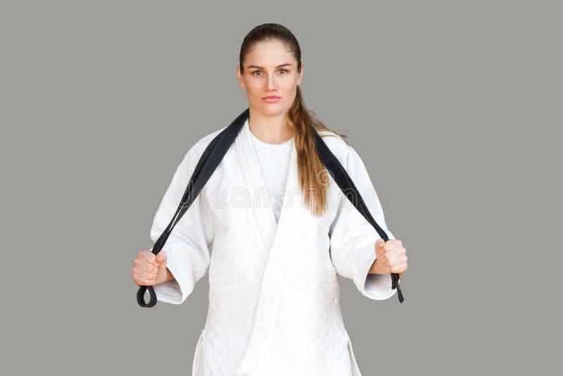 Zekere aantrekkelijke atletische vrouw in witte kimono die bevinden zich en stock foto's