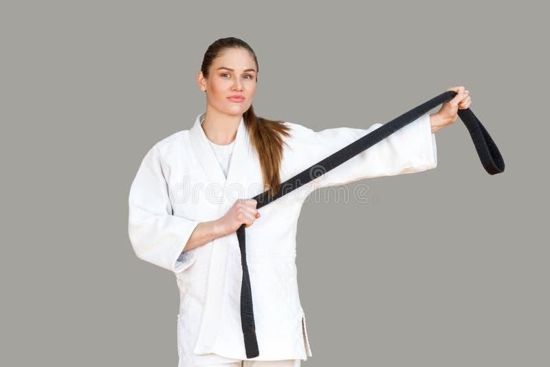 Zekere aantrekkelijke jonge atletische vrouw in witte kimonostandi royalty-vrije stock afbeelding