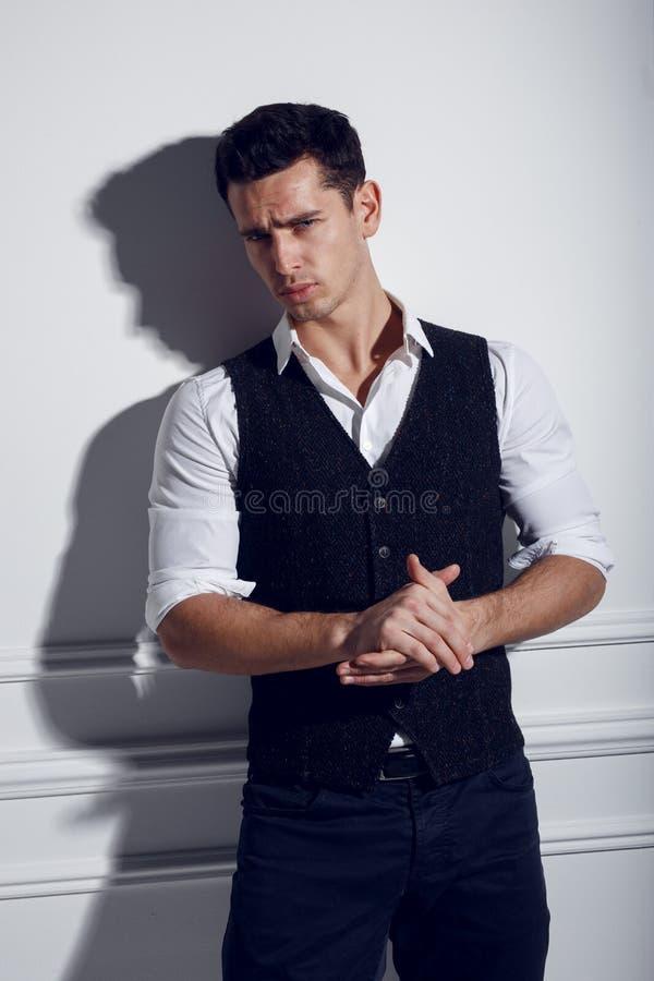 Zekere, aantrekkelijke jonge mens in elegante kleren dichtbij witte muur, die in studio, lichten stellen van studio stock afbeelding