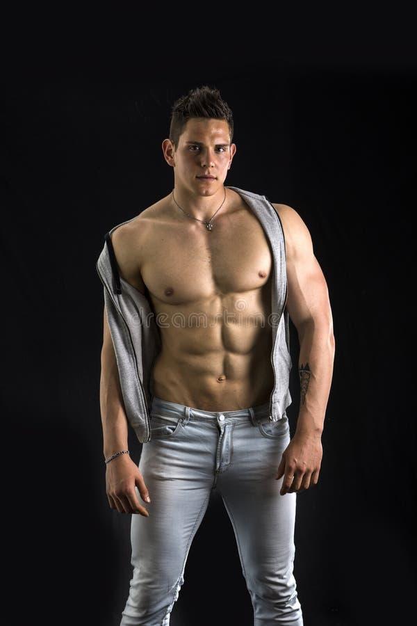 Zekere, aantrekkelijke jonge mens met open vest  stock afbeelding