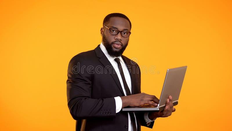 Zekere Afro-Amerikaanse laptop van de zakenmanholding en het kijken aan cameraopstarten stock foto's