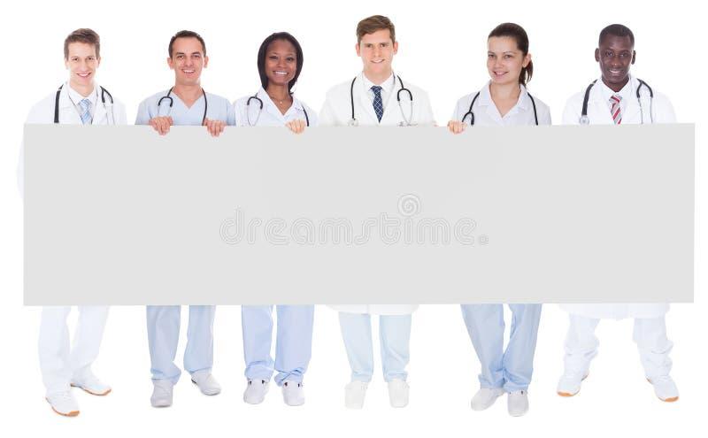 Zekere artsen die leeg aanplakbord houden stock afbeelding