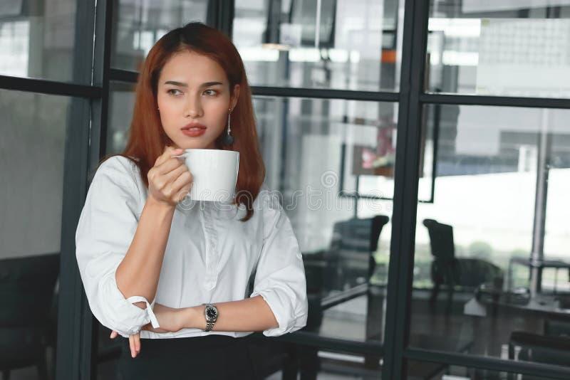 Zekere Aziatische onderneemster die en koffiekop in bureau bevinden zich houden Leiders bedrijfsvrouwenconcept royalty-vrije stock afbeeldingen