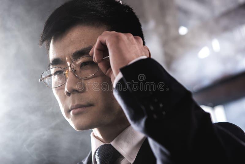 Zekere Aziatische zakenman die in oogglazen weg kijken stock fotografie