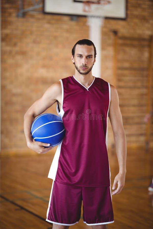 Zekere basketbalspeler die een basketbal houden royalty-vrije stock foto's