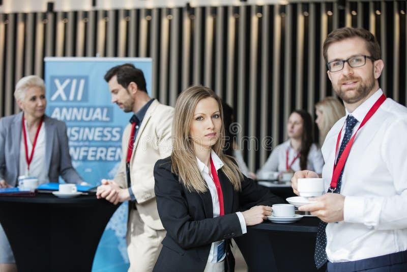 Zekere bedrijfsmensen die koffiekoppen houden bij hal in overeenkomstcentrum royalty-vrije stock afbeelding