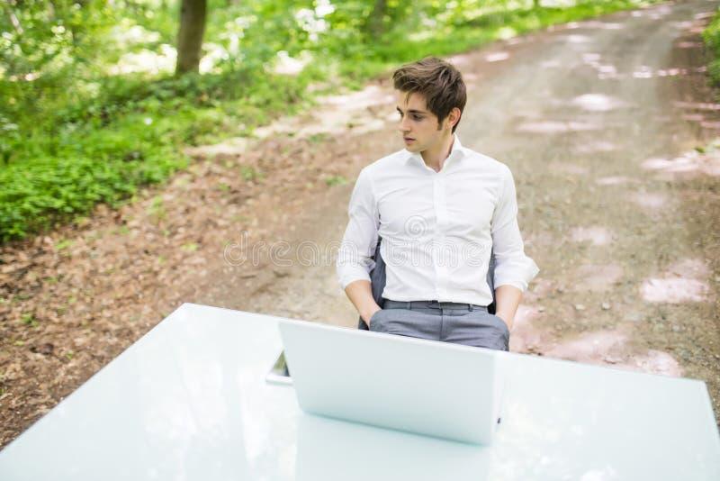 Zekere bedrijfsmensenzitting bij bureau op weg van groen bos Bedrijfsconcept stock fotografie