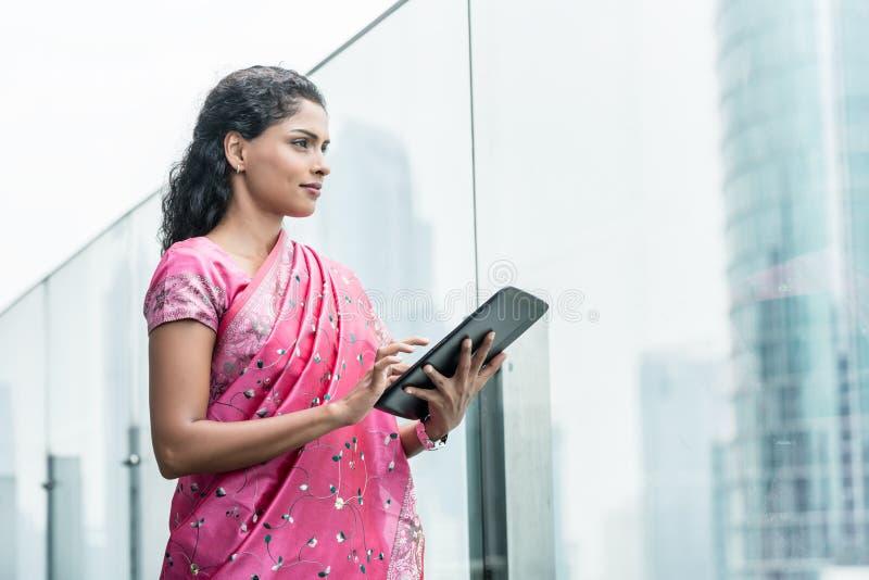 Zekere bedrijfsvrouw die een tabletpc in openlucht met behulp van royalty-vrije stock foto