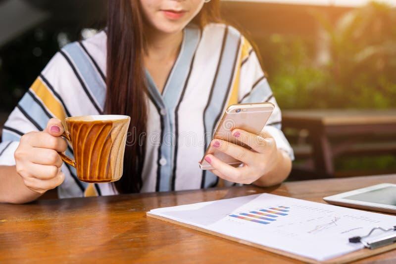 Zekere bedrijfsvrouw die in slimme vrijetijdskleding aan smartphone werken terwijl het zitten in creatief bureau stock foto's