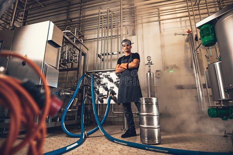 Zekere brouwer in schort bij brouwerijfabriek royalty-vrije stock fotografie