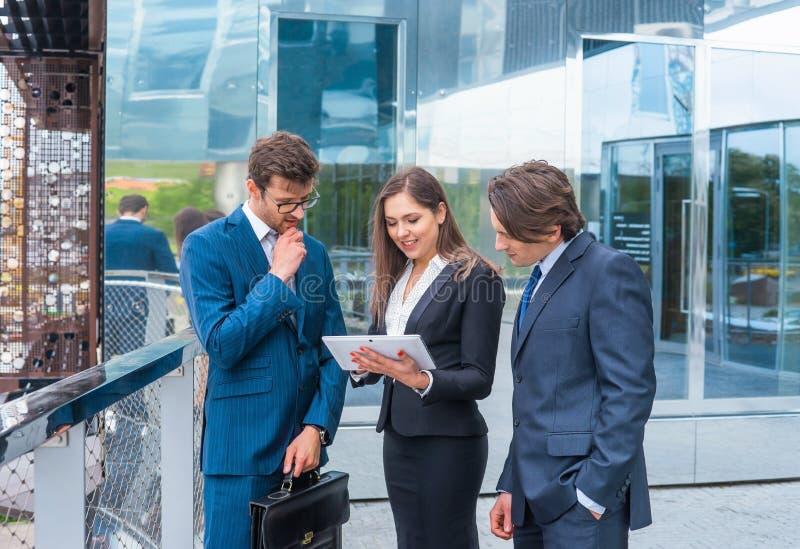 Zekere businesspersons die voor de moderne bureaubouw spreken De zakenlieden en de onderneemster hebben zaken royalty-vrije stock afbeelding