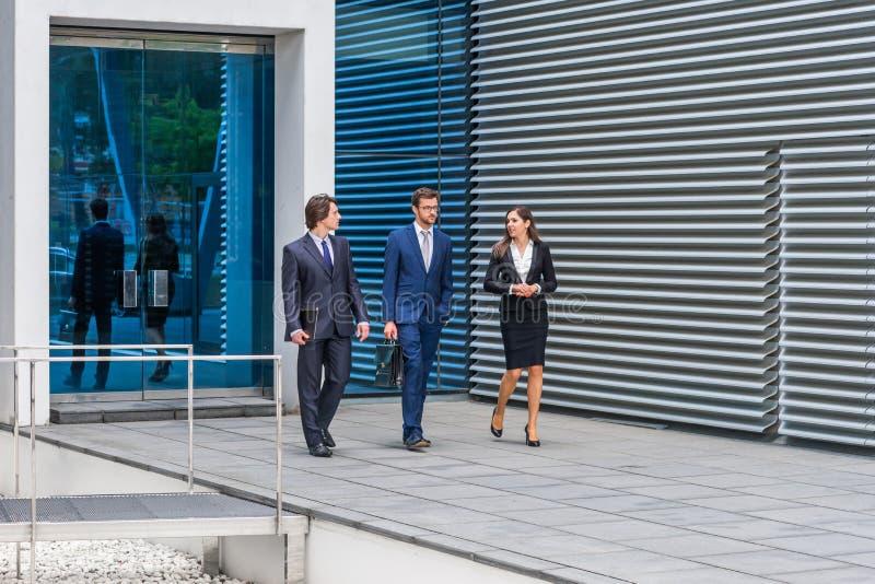 Zekere businesspersons die voor de moderne bureaubouw spreken De zakenlieden en de onderneemster hebben zaken stock foto's