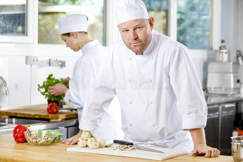 Zekere chef-kok die voedsel in grote keuken maken stock fotografie