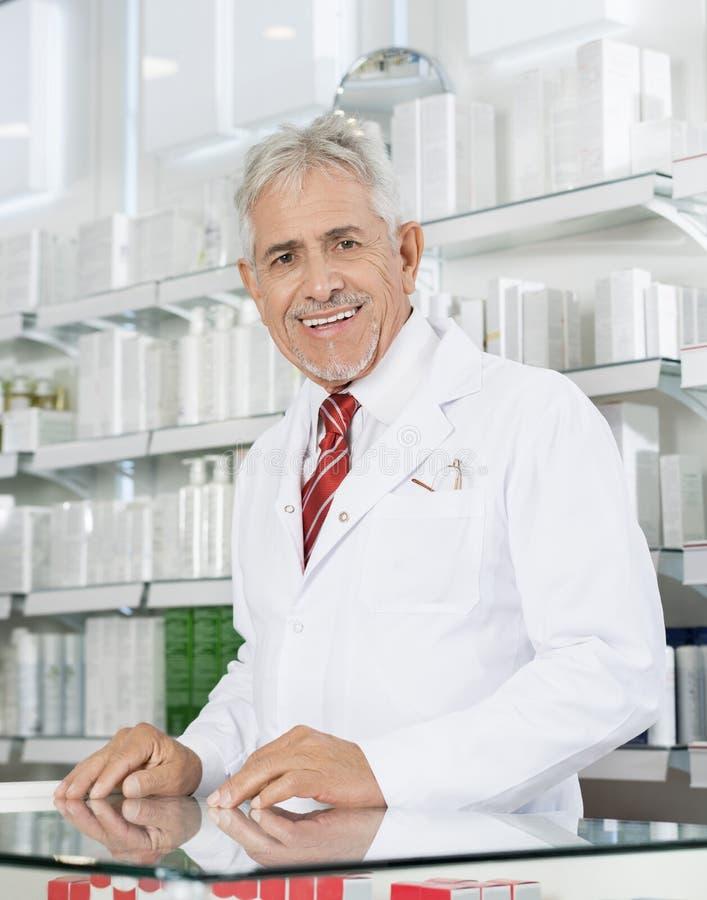 Zekere Chemicus Smiling At Counter in Apotheek stock fotografie