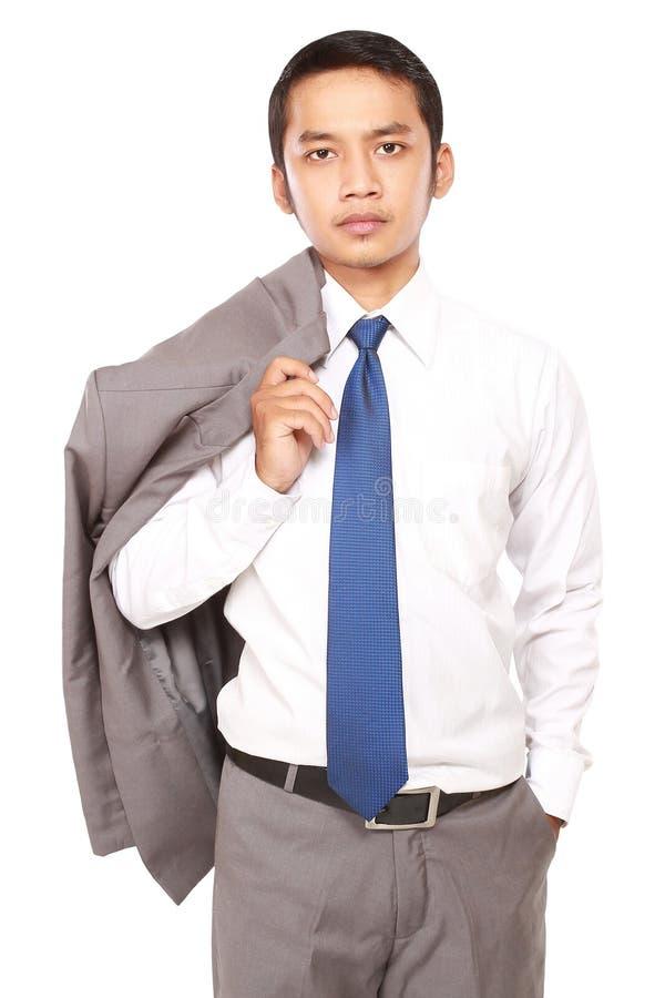 Zekere die zakenman met jasje over schouder wordt gedrapeerd stock fotografie