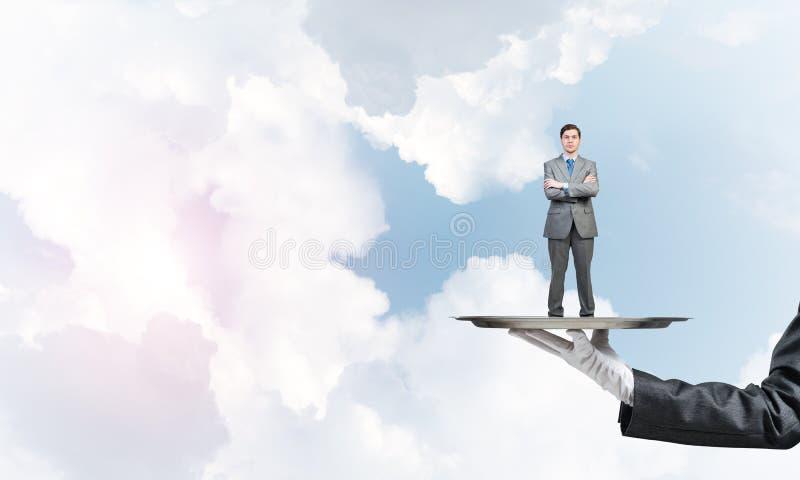Zekere die zakenman op metaaldienblad tegen blauwe hemelachtergrond wordt voorgesteld royalty-vrije stock fotografie
