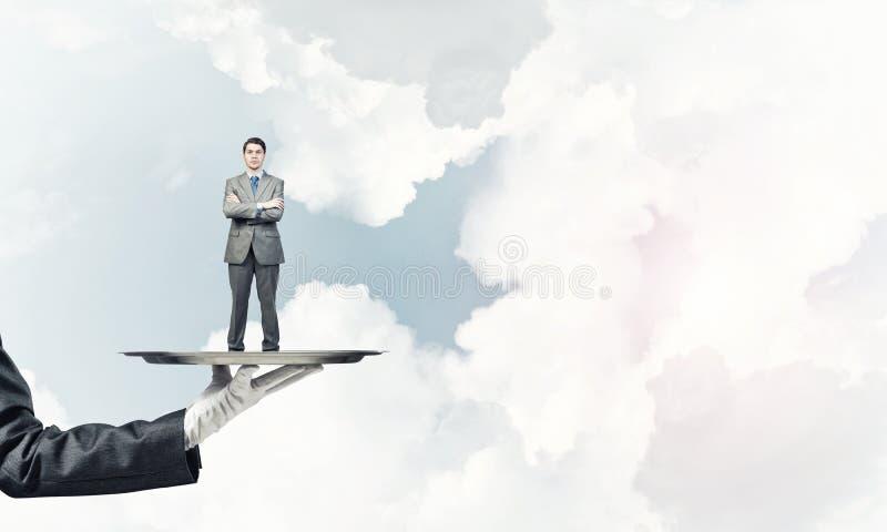 Zekere die zakenman op metaaldienblad tegen blauwe hemelachtergrond wordt voorgesteld stock afbeelding