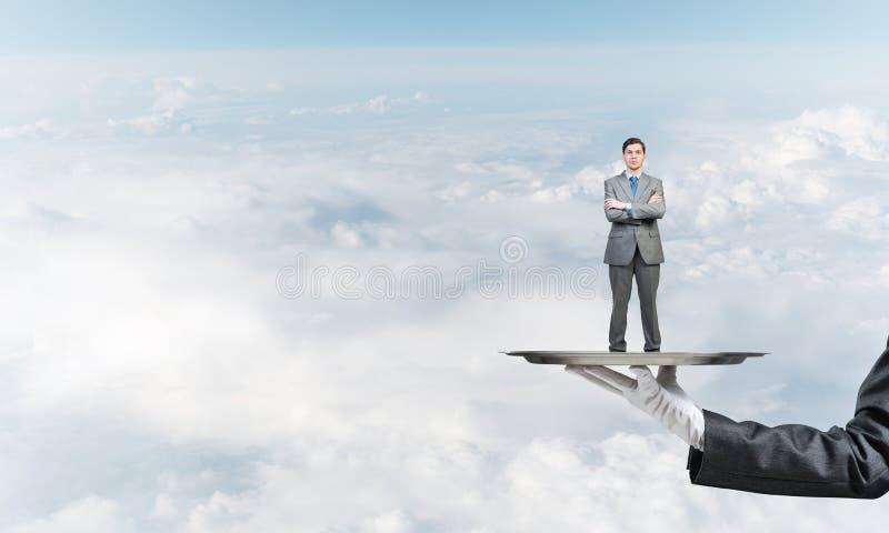 Zekere die zakenman op metaaldienblad tegen blauwe hemelachtergrond wordt voorgesteld royalty-vrije stock afbeelding