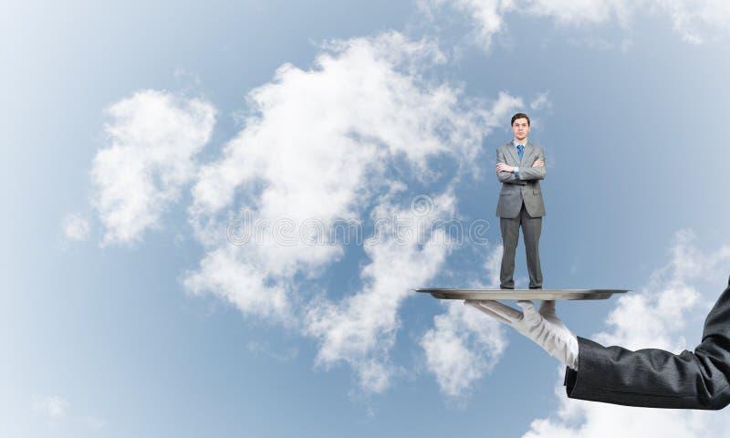 Zekere die zakenman op metaaldienblad tegen blauwe hemelachtergrond wordt voorgesteld royalty-vrije stock foto's