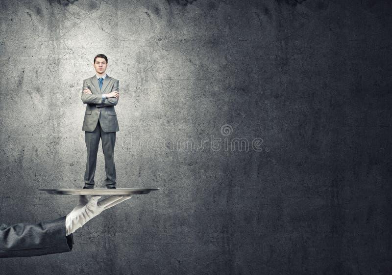 Zekere die zakenman op metaaldienblad tegen concrete muurachtergrond wordt voorgesteld stock foto