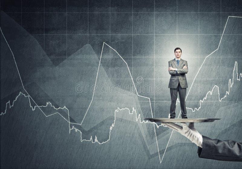 Zekere die zakenman op metaaldienblad tegen concrete muurachtergrond wordt voorgesteld met grafieken royalty-vrije stock afbeelding