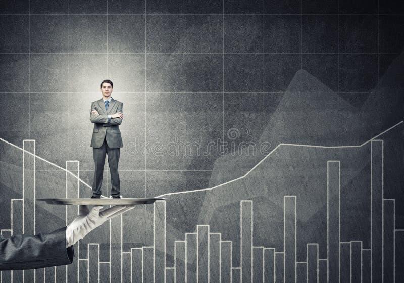 Zekere die zakenman op metaaldienblad tegen grafieken en diagrammenachtergrond wordt voorgesteld stock afbeeldingen