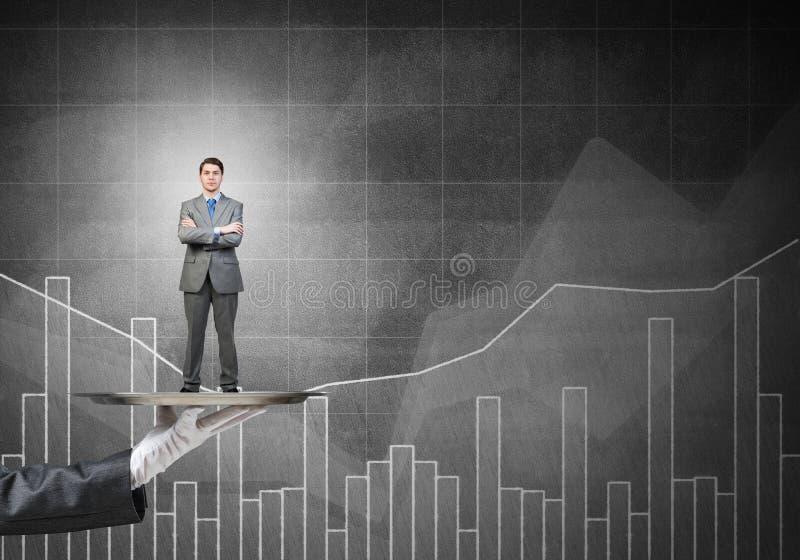 Zekere die zakenman op metaaldienblad tegen grafieken en diagrammenachtergrond wordt voorgesteld royalty-vrije stock afbeelding