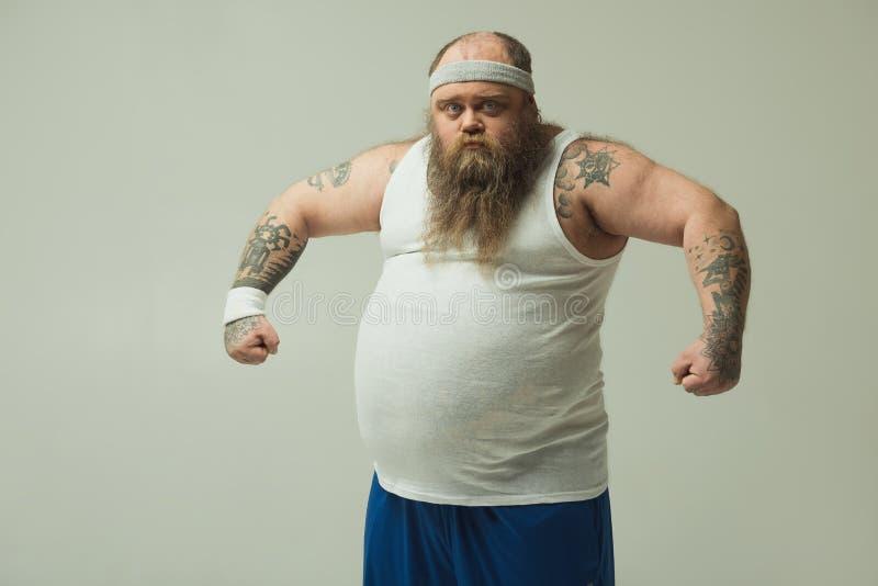 Zekere dikke kerel die zijn bicepsen met trots tonen stock fotografie