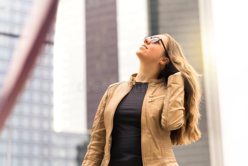 Zekere donkerbruine vrouw die in de stad lopen stock foto