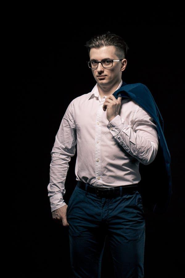 Zekere elegante bedrijfsmens die met glazen camera over zwarte studioachtergrond bekijken op de mens s houdt de schouder een jasj royalty-vrije stock afbeelding