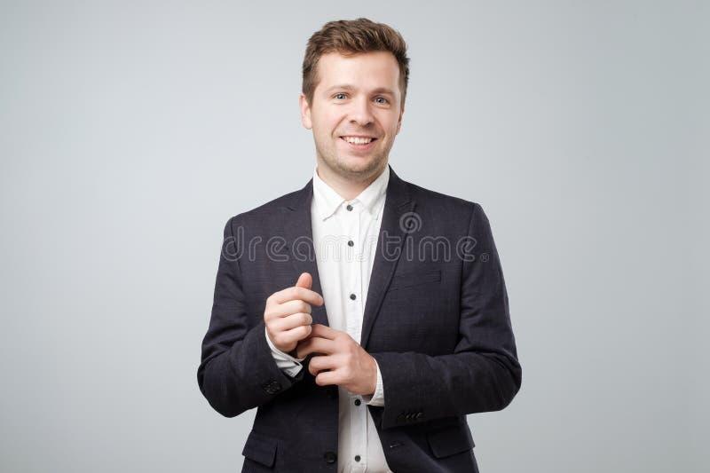 Zekere elegante knappe jonge mens die dragend een aardig kostuum bevinden zich stock fotografie