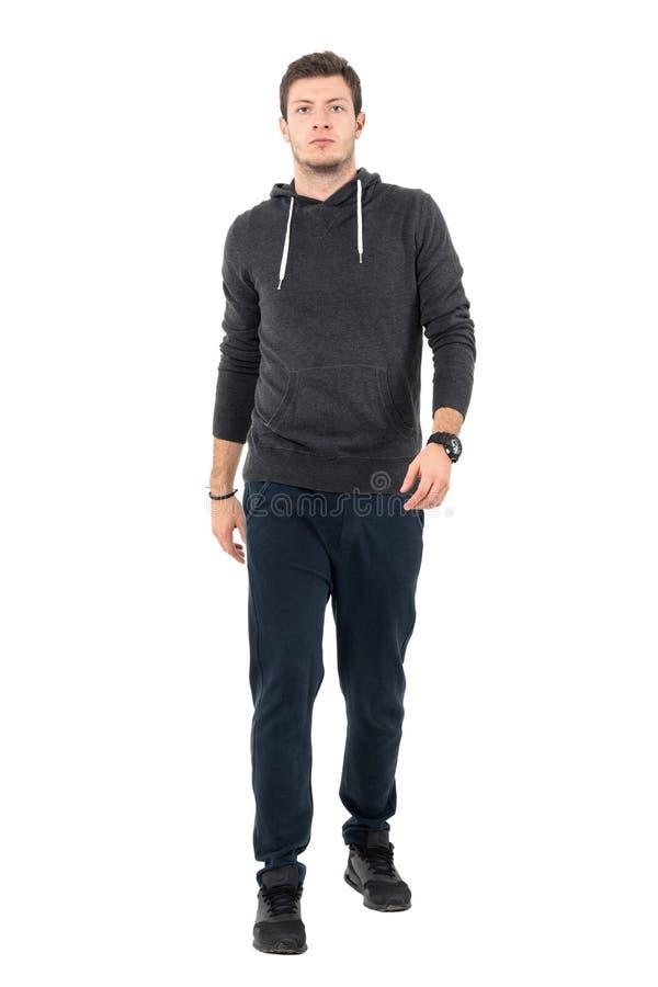 Zekere ernstige mens in sweatshirt en bovenkledij die naar camera lopen stock fotografie
