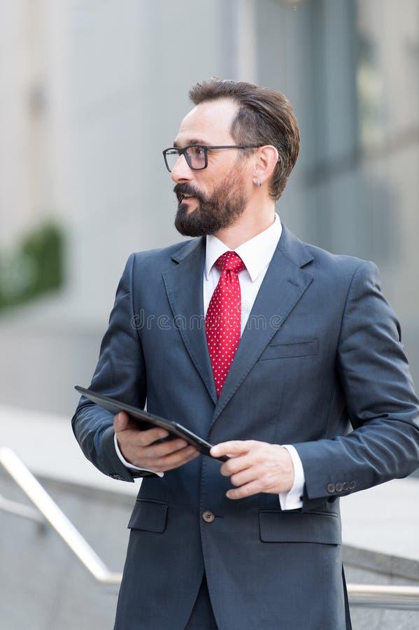 Zekere gebaarde mens die de afstand onderzoeken terwijl status met tablet stock fotografie