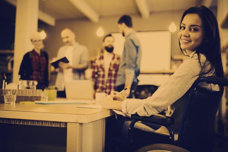 Zekere gehandicapte onderneemster die bij bureau schrijven stock foto's