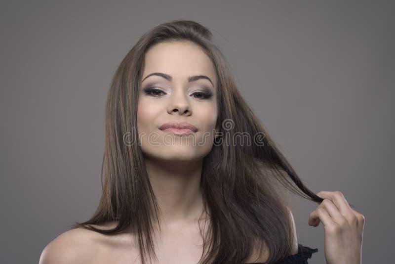Zekere gelooide schitterende vrouwelijke Latijnse schoonheid die bruin haar tollen en camera bekijken royalty-vrije stock afbeelding