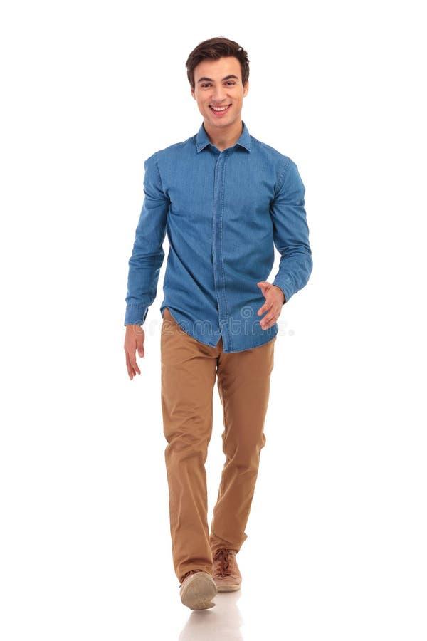 Zekere gelukkige jonge toevallige mens die vooruit lopen stock foto's