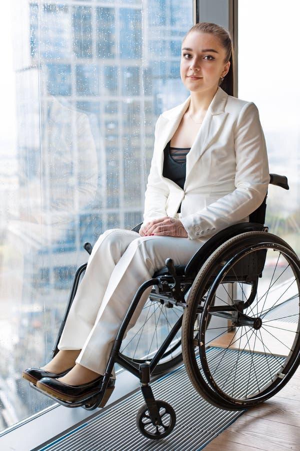 Zekere gelukkige onderneemster in rolstoel tegen de achtergrond van een panoramisch venster die de wolkenkrabbers overzien en stock foto's